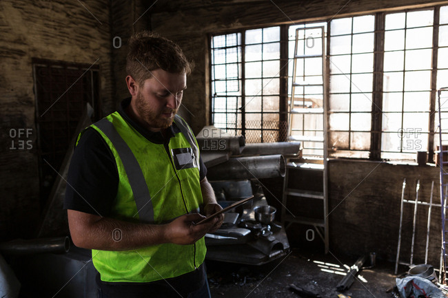 Concentrated worker using digital tablet in the junkyard