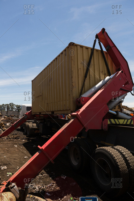 Close-up of crane lifting the heavy container at scrapyard