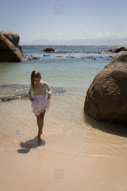 Girl playing in water at beach on a sunny day