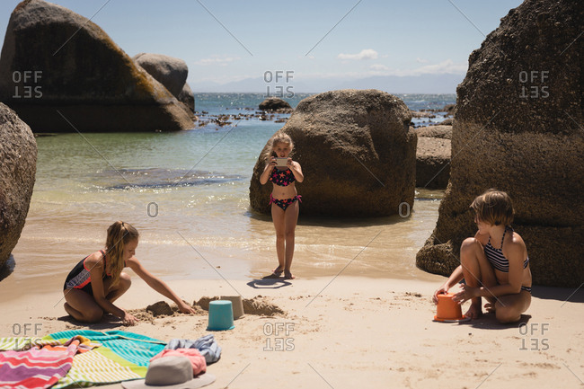 Girl taking picture of her siblings with mobile phone on beach