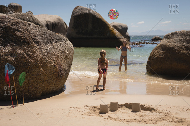 Siblings playing with ball in sea at beach