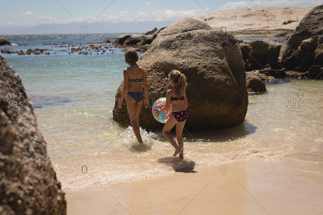 Siblings walking with ball in sea at beach