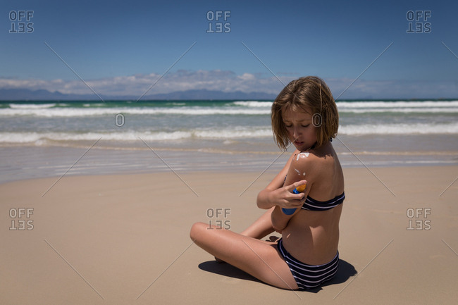 Teenage girl applying sunscreen lotion on back at beach