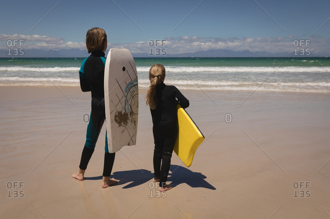 Rear view of siblings in wetsuit standing with surfboard on beach