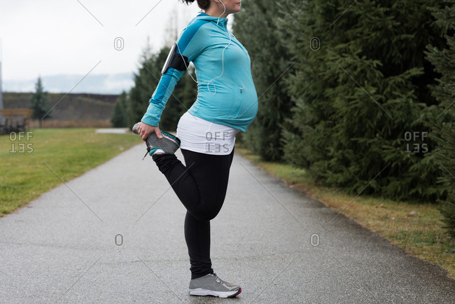 Pregnant woman performing stretching exercising in the park