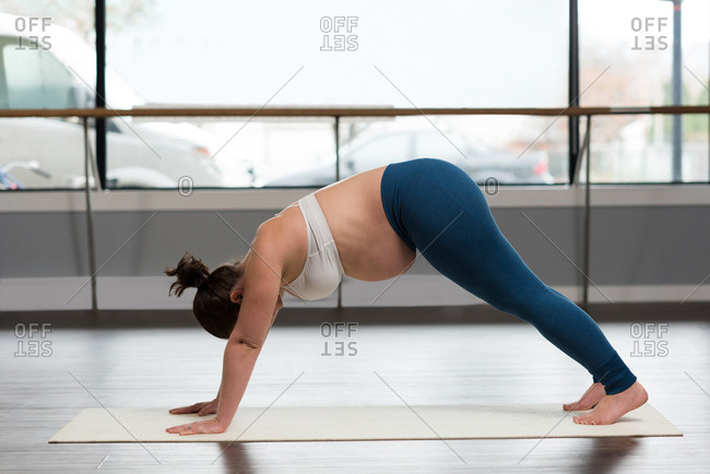 Pregnant woman exercising in living room at home