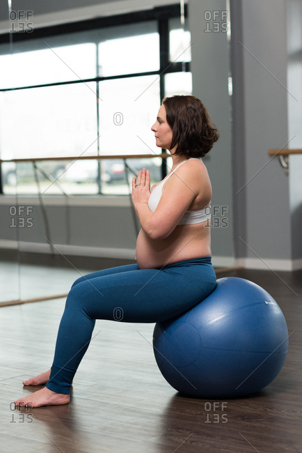 Pregnant woman performing yoga on exercise ball at home