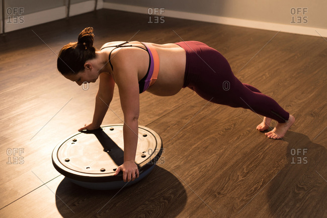 Pregnant woman exercising with bosu ball in living room at home