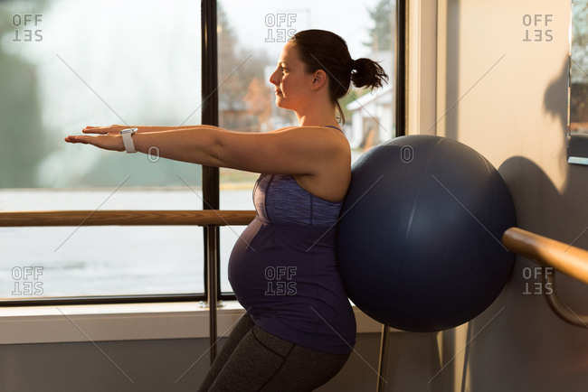 Pregnant woman exercising with exercise ball in living room at home