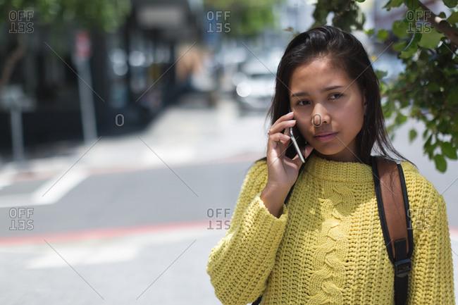 Teenage girl talking on mobile phone in city