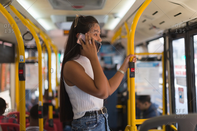 Teenage girl talking on mobile phone in the bus