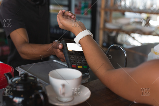 Teenage girl making payment through smart watch in restaurant