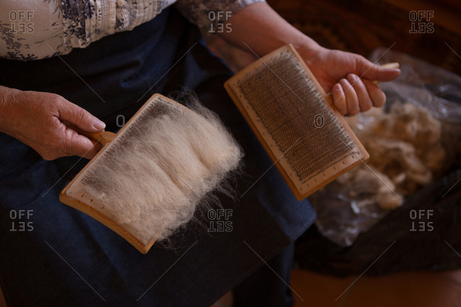 Mid section of senior woman using weaving brush at shop