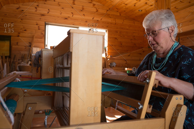 Active senior woman weaving silk at shop