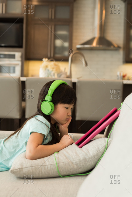 Woman with headphones using digital tablet at home