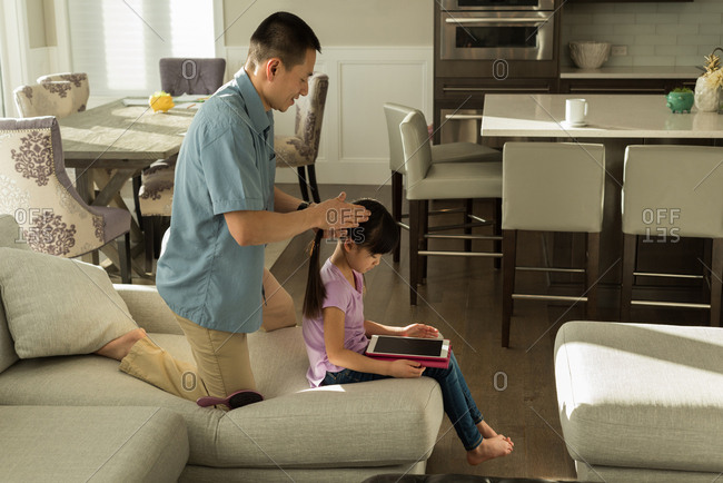 Girl using digital tablet while father combing her hair at home
