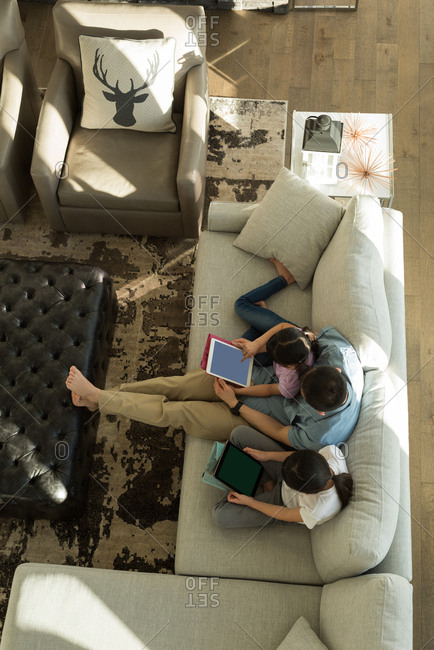 Overhead view of girls using digital tablet with her father in living room at home