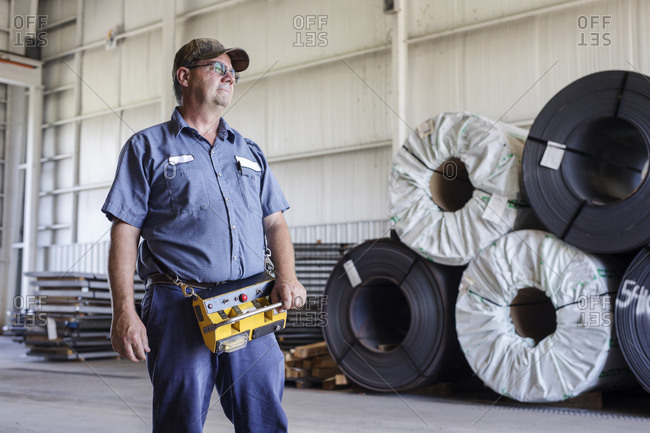 Confident worker with machine standing by rolled up metal sheets at Steel Mill