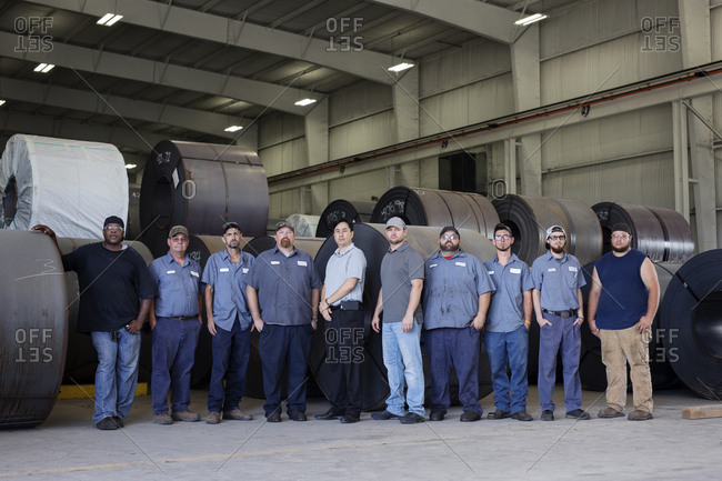 Portrait of confident manual workers standing against rolled up metal sheets in warehouse