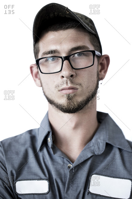 Portrait of confident manual worker wearing cap and eyeglasses against white background