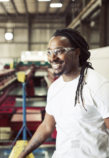 Cheerful blue collar worker wearing protective eyeglasses while working in steel industry