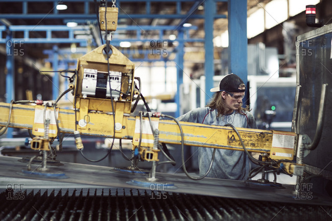 Steel worker using machinery while working in factory