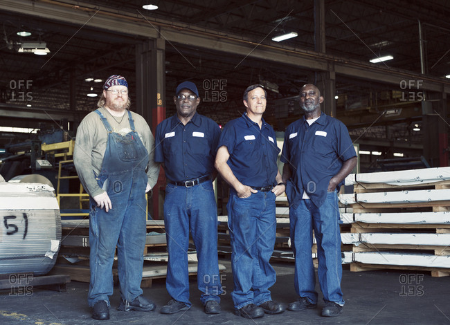 Full length portrait of coworkers standing against manufacturing objects in industry