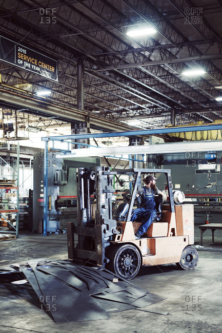 Male worker driving forklift by steel sheets at industry