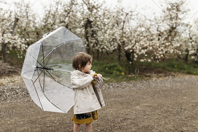 Little girl holding a transparent umbrella on her shoulder