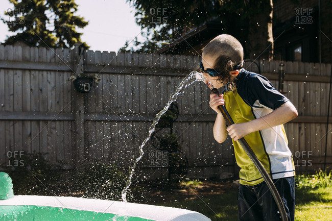 Young boy drinking from a hose in backyard