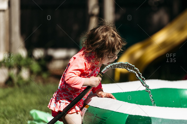 Young girl trying to drink from a hose in the backyard
