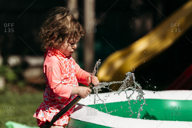 Young girl sticking fingers in running hose