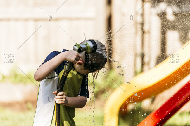Young boy showering with hose in backyard