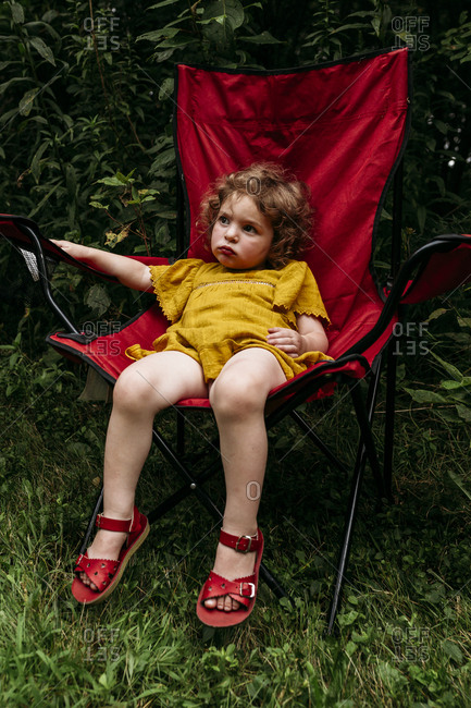 Tired little girl slouching in lawn chair