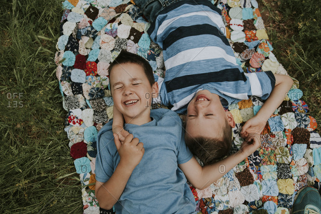 Two boys laying down, holding hands and laughing