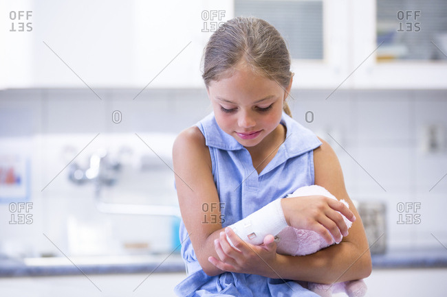 Girl examining bandaged arm