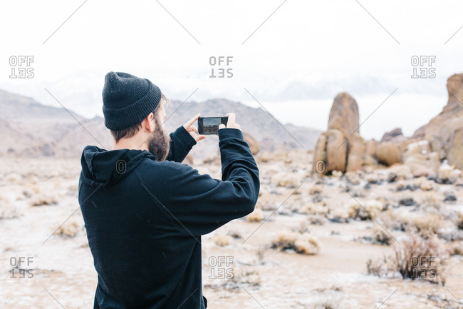 Man taking picture of mountains with cell phone