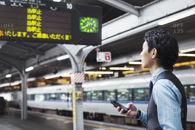 Businessman wearing blue shirt and vest standing on train station platform, holding mobile phone