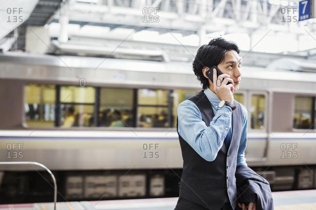 Businessman wearing blue shirt and vest standing on train station platform, talking on mobile phone