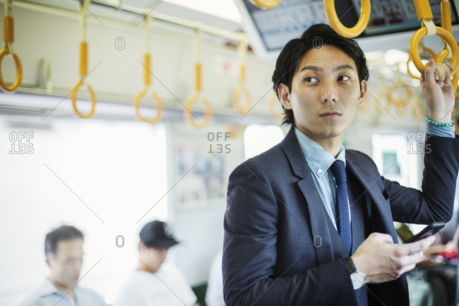 Businessman wearing suit standing on a commuter train, holding mobile phone