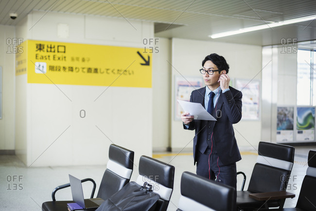 Businessman wearing suit and glasses standing at train station, holding papers, using headphones