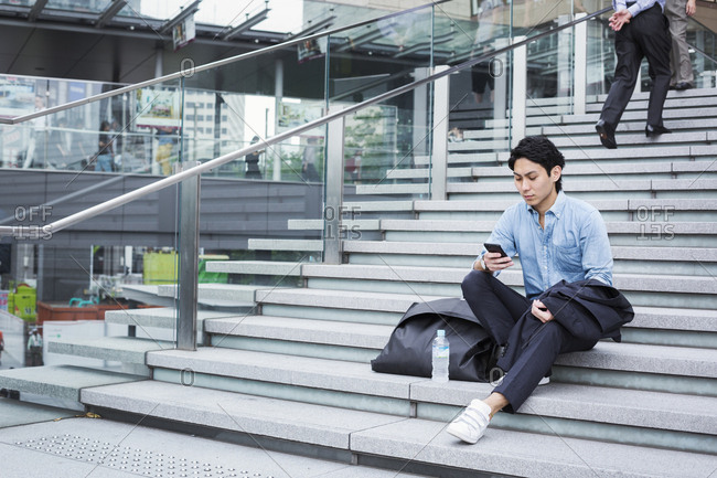 Businessman wearing blue shirt sitting outdoors on steps, looking at mobile phone