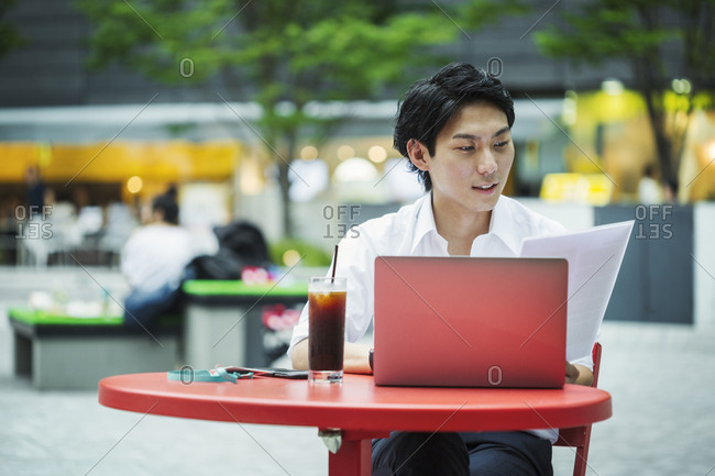 Businessman wearing white shirt sitting outdoors at red table, holding papers, working on laptop