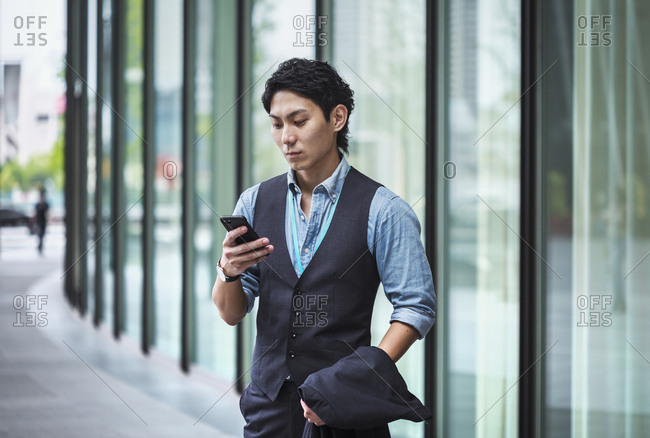 Businessman wearing blue shirt and vest standing outdoors, holding mobile phone