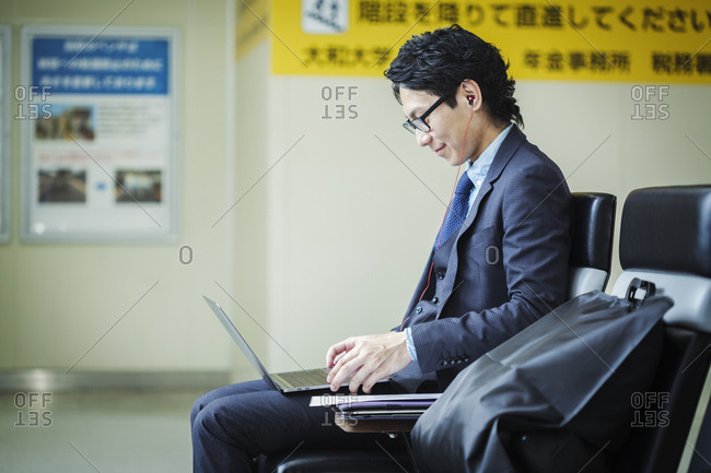 Businessman wearing suit and glasses sitting at train station, working on laptop