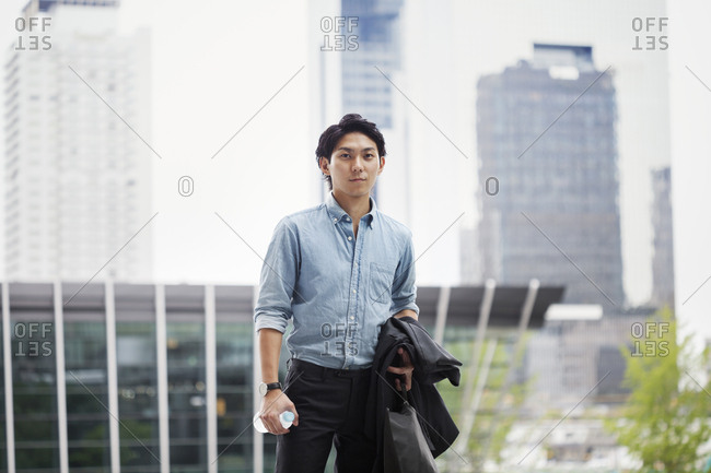 Businessman wearing blue shirt standing outdoors, holding jacket, briefcase and bottle of water