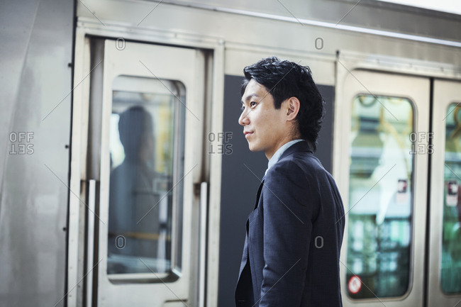 Businessman wearing suit standing at train station platform