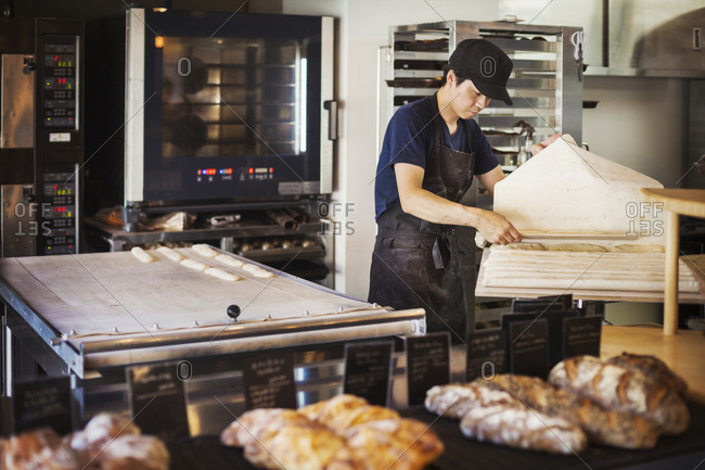 Man working in a bakery, preparing large tray with dough for rolls, oven in the background
