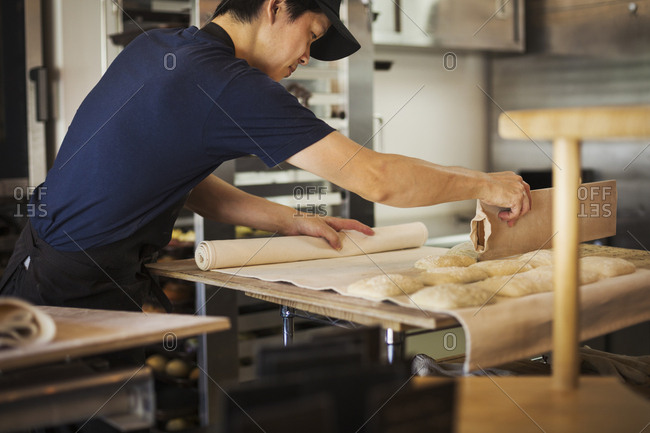 Man working in a bakery, cutting dough for rolls with large cutter