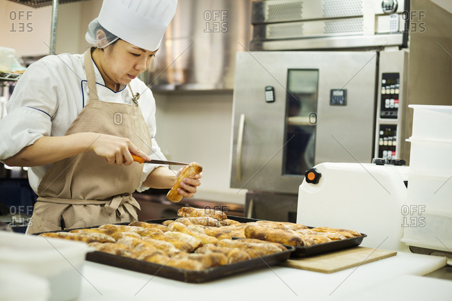 Woman wearing chef's hat and apron working in a bakery, slicing freshly baked rolls on large trays